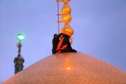 تصویری  رپورٹ حرم حضرت معصومہ سلام اللہ علیھا کے گنبد مبارک پر پرچم حرم  امام  حسین  (ع) نصب
