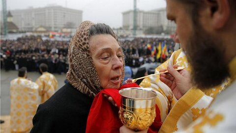 Believers from the Orthodox Cathedral in Romania shared with the same spoon