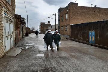 تصاویر/ توزیع مواد ضد عفونی توسط طلاب قرارگاه جهادی حوزه علمیه همدان در زیر بارش باران