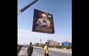 فیلم   نصب تصویر بزرگی از حاج قاسم و ابومهدی در مسیر کربلا