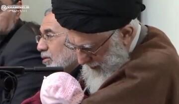 فیلم   اذان گفتن رهبر معظم انقلاب در گوش فرزند سوم شهید مدافع حرم محمد بلباسی