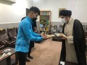 """اهداء یک جلد قرآن کریم به سرپرست گروه موسیقی دزفول توسط """"امام جمعه"""""""