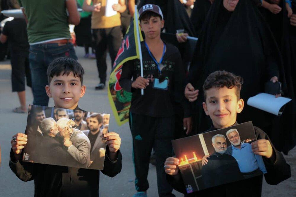 تصاویر شهدای مقاومت در دستان زائران اربعین