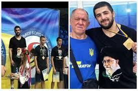 Ukrainian wrestler stands on champ's podium with singlet drawn with image of Ayatollah Khamenei