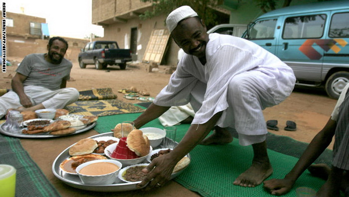 مردی در حال قرار دادن سینی غذا بر سر سفره افطار در شرق خارطوم پایتخت سودان