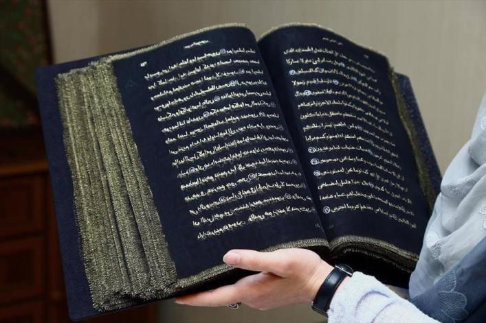 قرآن کریم با استفاده از رنگهای طلایی و نقرهای بر روی پارچه ابریشمی