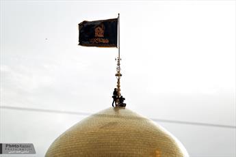 اهتزاز پرچم عزاي زینبی بر فراز گنبد حرم رضوي